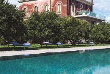 Une vaste piscine au milieu d'un parc d'orangers et de citronniers, une vue sur l'Etna et le golfe de Taormine, une imposante bâtisse aux tons ocre : aucun doute, nous sommes en Sicile.